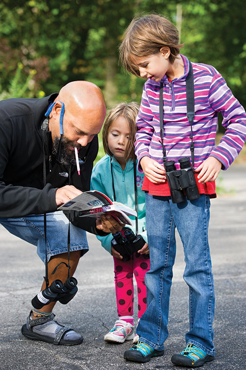 Naturalist David Wright helps two young birdwatchers