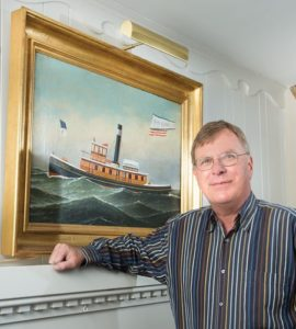 Jim Holcomb standing before a painting by the Danish American artist Antonio Jacobsen.