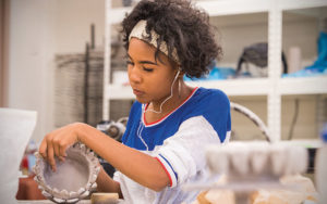 Shaker student making pottery