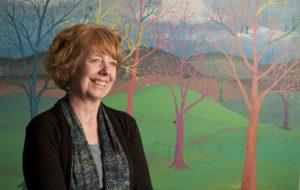 Betsie Norris standing in front of mural by Stephanie Miller
