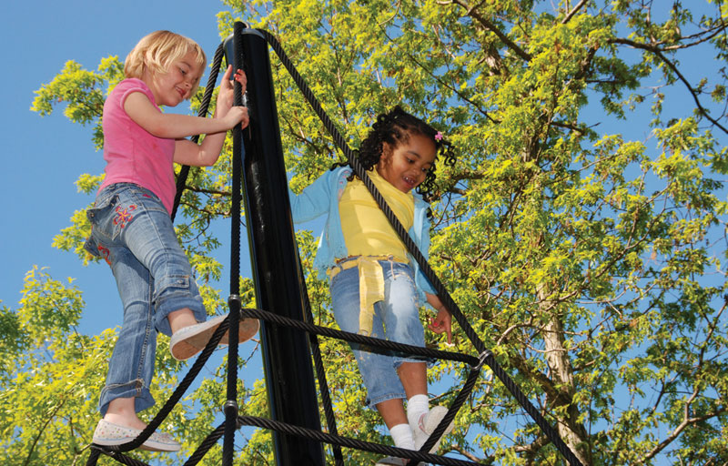 Children playing on the spider web structure at Shaker's Horseshoe Lake Park.