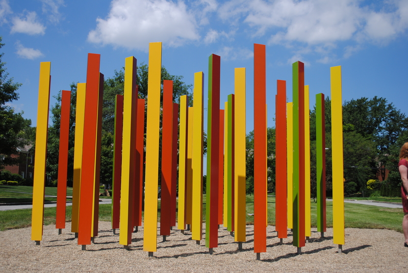 Colorful triangular stainless steel posts are painted a different color on each face, providing a changing view depending on the viewer's perspective.
