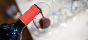 Red wine pouring out of bottle into glass