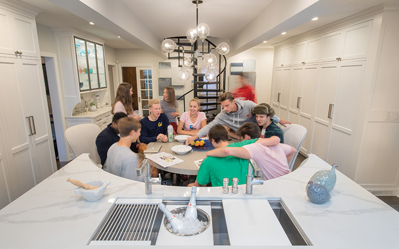 View of a renovated Shaker kitchen with teenagers at the table.