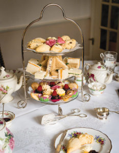 Three-tiered serving tray with scones, finger sandwiches and other sweet treats.