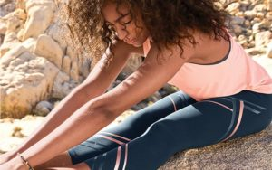 Woman stretching in New Balance athletic gear