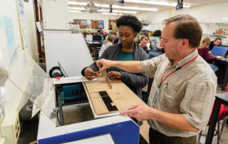 Shaker Heights High School senior Corin Manning and Engineering teacher Dr. Joe Marencik work on a design project using a laser cutter.