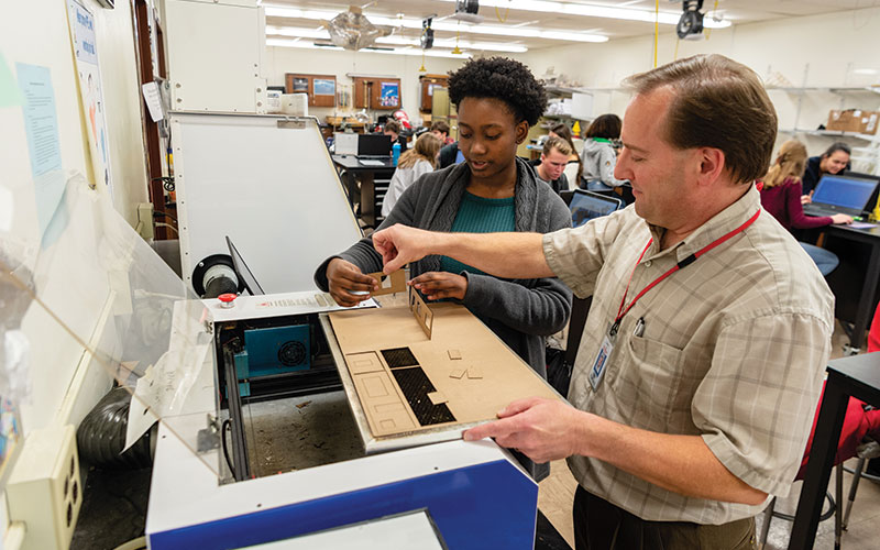 Shaker Heights High School senior Corin Manning and Engineering teacher Dr. Joe Marencik work on a design project using a laser cutter.
