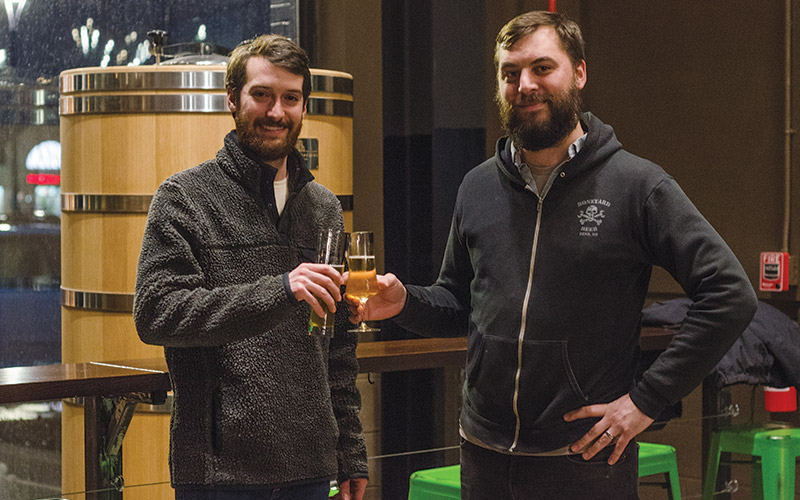 Andrew Martahus, left, raises a glass with Jason Kallicragas of BottleHouse.