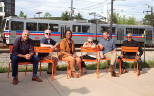 Members of the Public Art Task Force seated on an installation of orange chairs in the Van Aken District