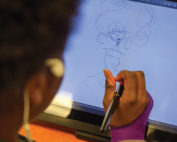 Shaker High artist drawing on a tablet