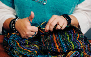 Close up of Pam Berkson, owner of Around the Table Yarns, working on a project