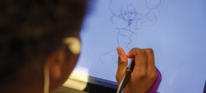 Shaker High student drawing on computer tablet