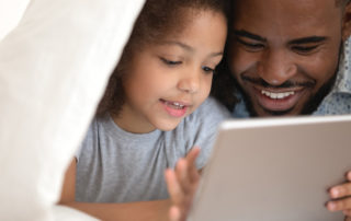 Dad and daughter reading on iPad