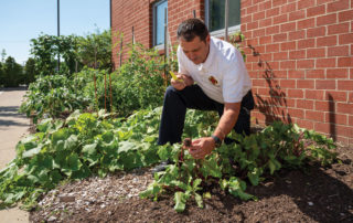 Battalion Chief Frank Zugan works in the garden at Fire Station 1.