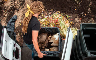 Employee of Rust Belt Riders dumping compost at its facility