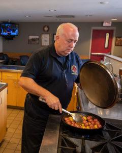 Firefighter Chuck Huddleston prepares the community meal.