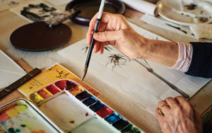 Close up of artist Anna Hsu working on a watercolor